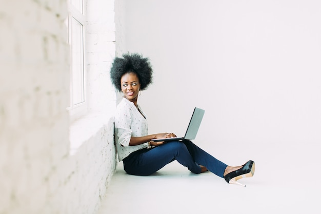 Young african american business woman using the laptop, while sitting on the floor near a big window