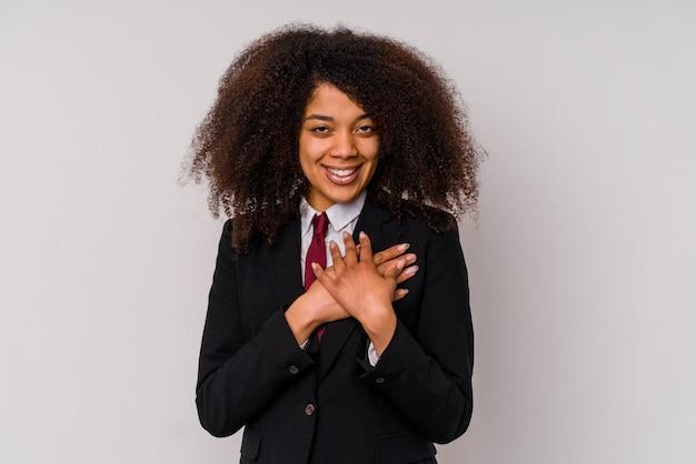 白い背景にスーツを着た若いアフリカ系アメリカ人のビジネスウーマンは、手のひらを胸に押し付けながら親しみやすい表情をしている.愛の概念。
