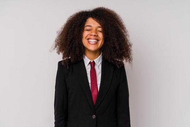 白い背景で隔離のスーツを着て若いアフリカ系アメリカ人のビジネス女性は笑って目を閉じ、リラックスして幸せな気分になります。