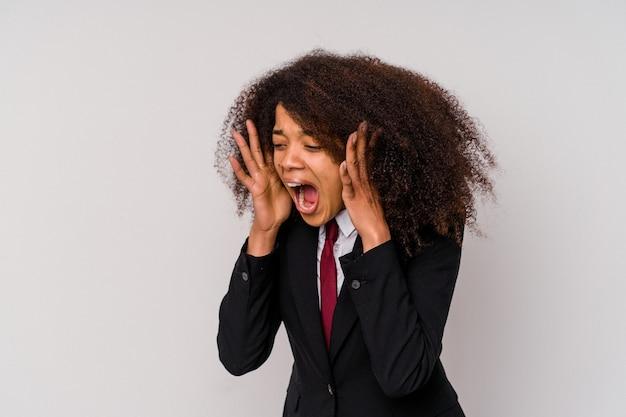 Молодая афро-американская бизнес-леди в костюме, изолированном на белом фоне, громко кричит, держит глаза открытыми и руки напряженными.