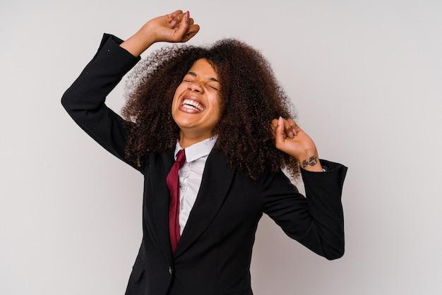 Молодая афро-американская бизнес-леди в костюме, изолированном на белом, празднует особый день, прыгает и поднимает руки с энергией.