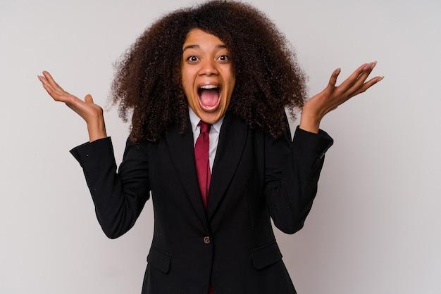 Молодая афро-американская бизнес-леди в костюме, изолированном на белом, празднует победу или успех, он удивлен и шокирован.