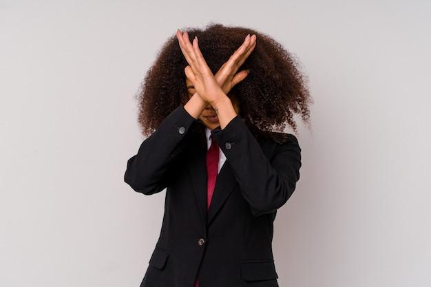 両腕を組んで、白で隔離のスーツを着ている若いアフリカ系アメリカ人のビジネスウーマン、否定の概念。