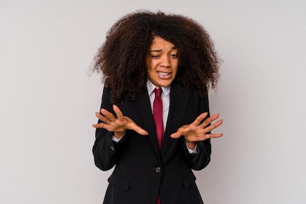 嫌悪感のジェスチャーを示す誰かを拒否する白で隔離のスーツを着ている若いアフリカ系アメリカ人のビジネスウーマン。