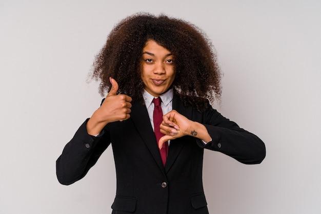 親指を上と親指を下に示す白で隔離のスーツを着ている若いアフリカ系アメリカ人のビジネスウーマン、難しい選択の概念