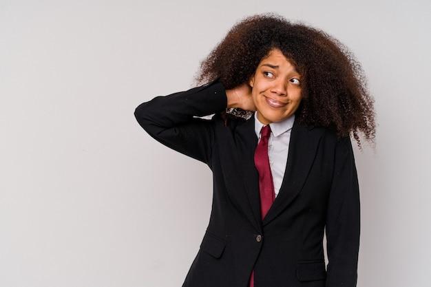 Молодая афро-американская бизнес-леди в костюме, изолированном на белом, касаясь затылка, думая и делая выбор.