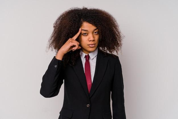 指で寺院を指している白い壁に隔離されたスーツを着て、考えて、タスクに焦点を当てた若いアフリカ系アメリカ人のビジネス女性。