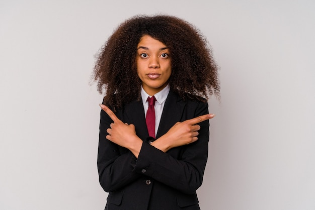 Young african american business woman wearing a suit isolated on white background points sideways, is trying to choose between two options.
