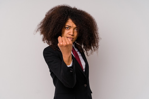 Young african american business woman wearing a suit isolated on white background showing fist to camera, aggressive facial expression.