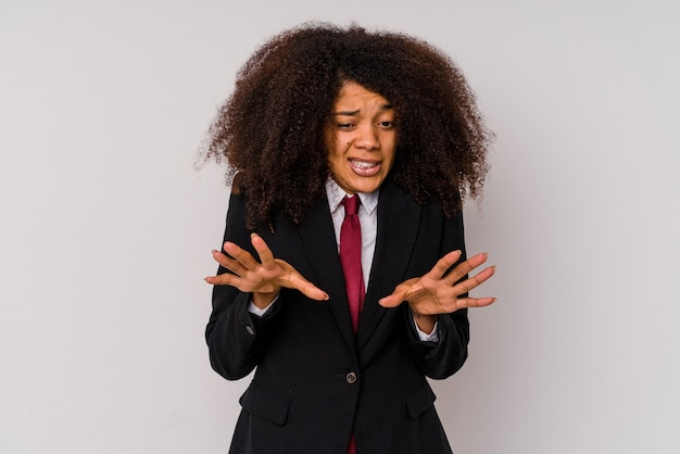 Young african american business woman wearing a suit isolated on white rejecting someone showing a gesture of disgust.