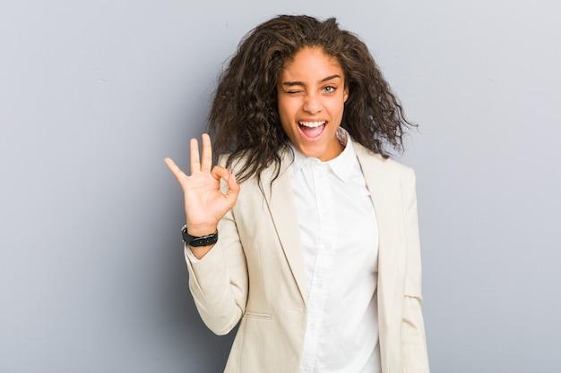 Молодая афро-американская бизнес-леди подмигивает и держит рукой хороший жест.