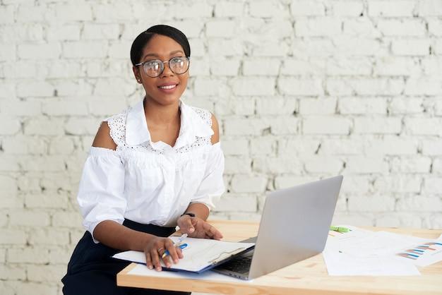 現代のオフィスで若いアフリカ系アメリカ人のビジネスマン。テーブルに一人で座っているラップトップでオンラインで作業している眼鏡をかけている若いアフリカの女性の笑顔。