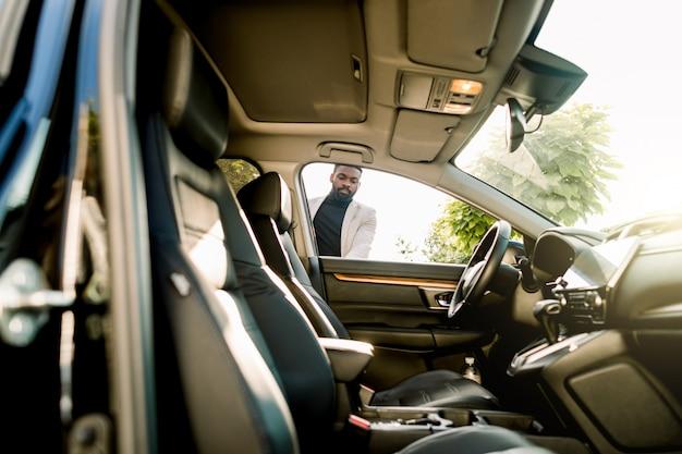 若いアフリカ系アメリカ人のビジネスマンが彼の新しい車のドアを開けます。サイドビュー、晴れた日