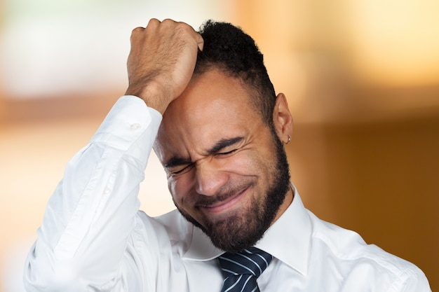 Young african-american businessman suffering from headache after hard working day