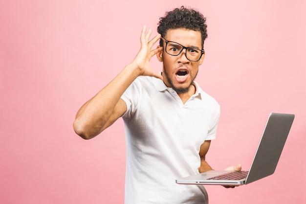 コンピューターのラップトップを使用して若いアフリカ系アメリカ人のビジネスマンは怒りでイライラして欲求不満の叫び