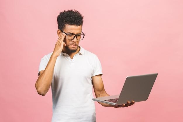 コンピューターのラップトップを使用してイライラして欲求不満の若いアフリカ系アメリカ人の実業家
