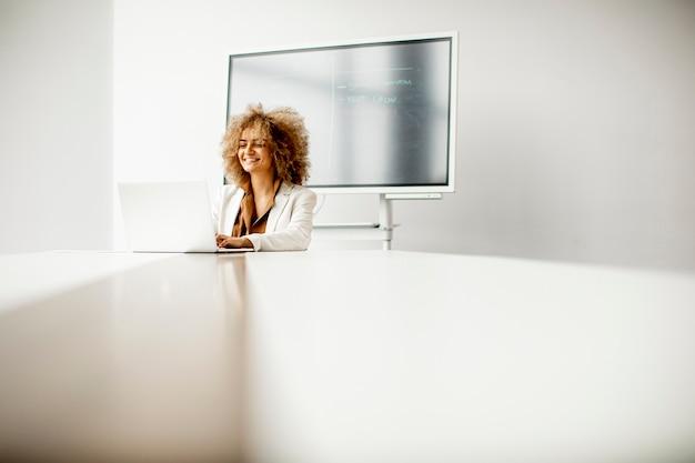 Молодой афро-американский бизнесмен сидит и работает на ноутбуке в современном офисе