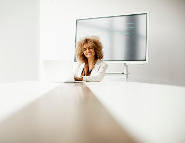 Young african american businesswoman sitting and working on laptop in the modern office