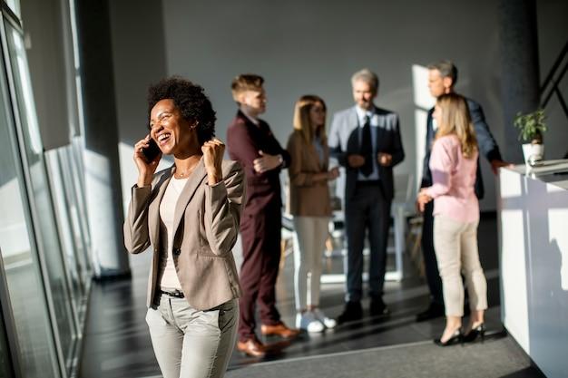 Молодой афро-американский бизнесмен, стоя и используя мобильный телефон в современном офисе