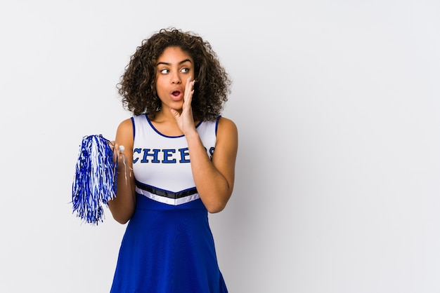 Young african american cheerleader woman isolated is saying a secret hot braking news and looking aside