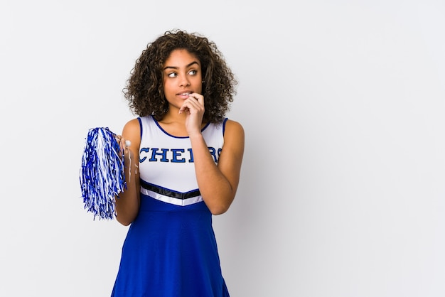 Young african american cheerleader woman isolated relaxed thinking about something looking at a copy space.