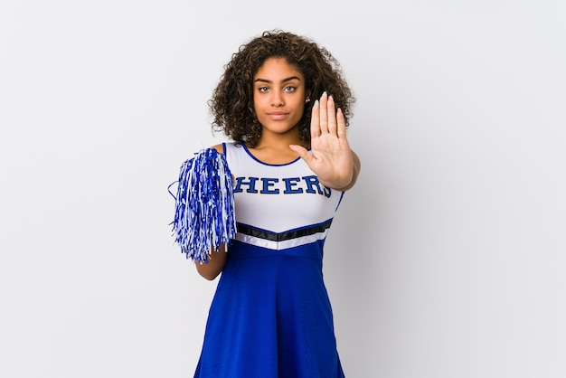Молодая афро-американская женщина чирлидера изолировала стоя с протянутой рукой, показывая знак остановки, предотвращая вас.