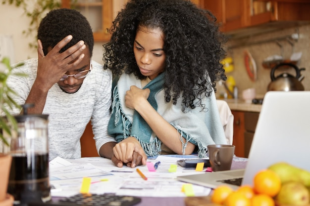 Young african-american couple with many debts calculating gas and electricity bills