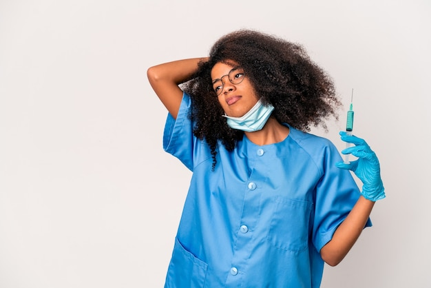 Young african american curly doctor woman holding a syringe touching back of head, thinking and making a choice.