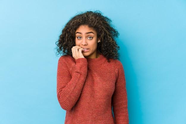 Молодая афро-американская женщина с вьющимися волосами кусает ногти, нервничает и очень волнуется.