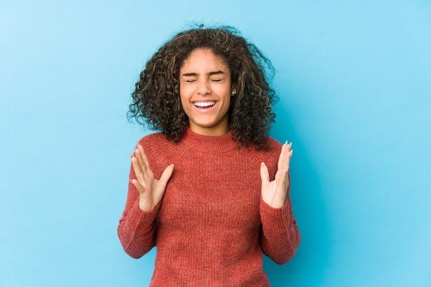 若いアフリカ系アメリカ人の巻き毛の女性はたくさん笑ってうれしそうです。幸福の概念。