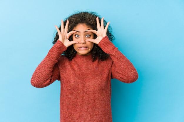 Молодая афро-американская женщина вьющиеся волосы держа глаза раскрытая для того чтобы найти возможность успеха.