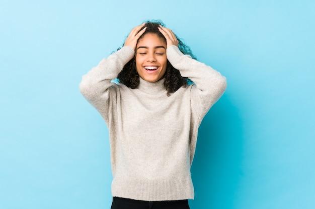 若いアフリカ系アメリカ人の巻き毛の女性は頭の上に手を維持して嬉しそうに笑います。
