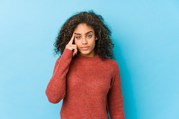 Young african american curly hair woman pointing temple with finger, thinking, focused on a task.