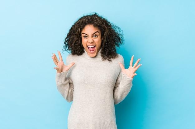 怒りで叫んでいる若いアフリカ系アメリカ人の巻き毛の女性。