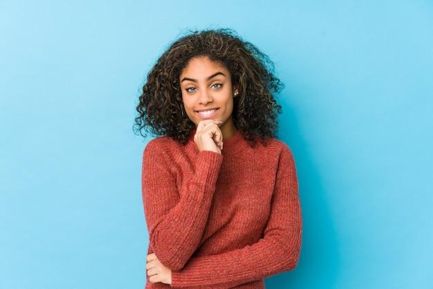 若いアフリカ系アメリカ人の巻き毛の女性の笑顔で幸せと自信を持って、あごに手で触れます。