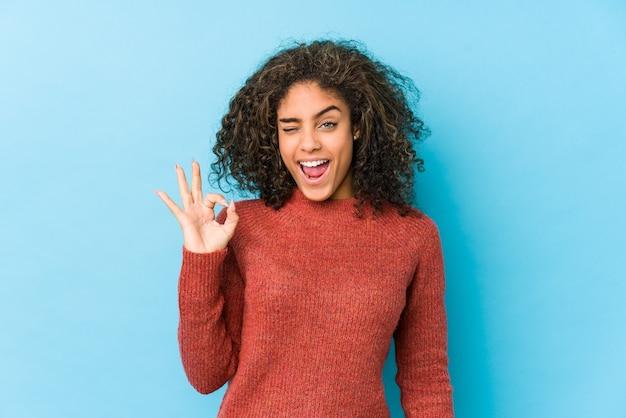 Молодая афро-американская женщина с вьющимися волосами подмигивает и держит рукой жест.