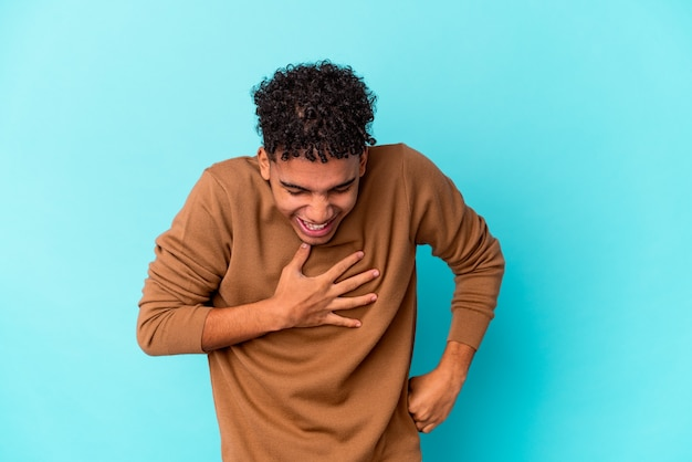Young african american curly man isolated on blue laughing keeping hands on heart, concept of happiness.