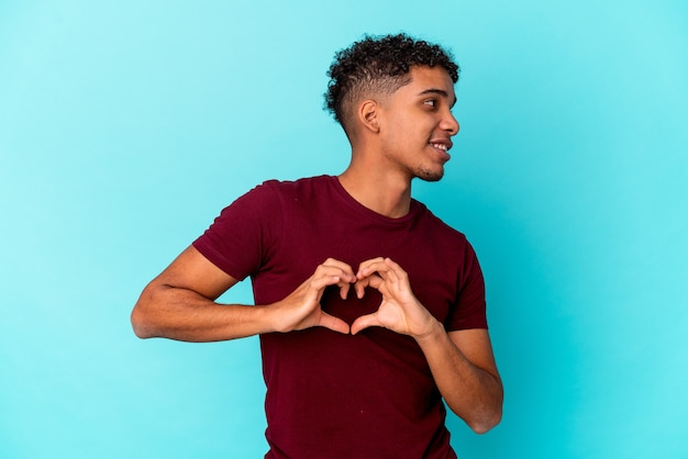 Young african american curly man isolated on blue smiling and showing a heart shape with hands.