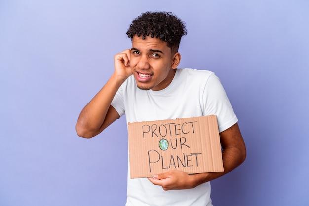 孤立した若いアフリカ系アメリカ人の巻き毛の男は、手で耳を覆っている私たちの惑星を保護します。