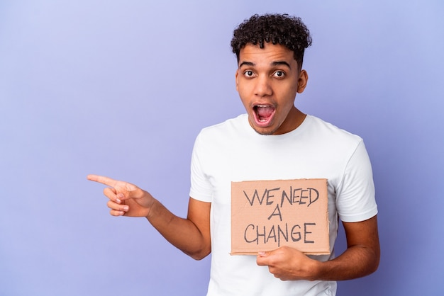 Young african american curly man isolated holding a we need a change cardboard pointing to the side