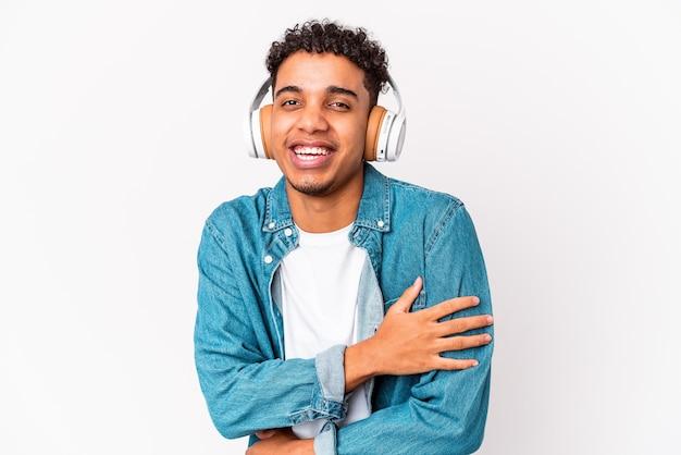 Молодой афро-американский кудрявый мужчина изолирован, слушая музыку в наушниках, громко смеется, держа руку на груди.