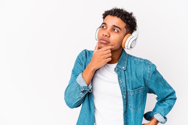 若いアフリカ系アメリカ人の巻き毛の男は、疑わしいと懐疑的な表現で横向きにヘッドフォンで音楽を聴いて孤立しました。
