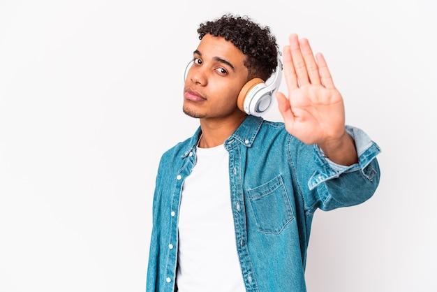 Молодой афро-американский кудрявый мужчина изолирован, слушая музыку в наушниках, стоя с протянутой рукой, показывая знак остановки, предотвращая вас.