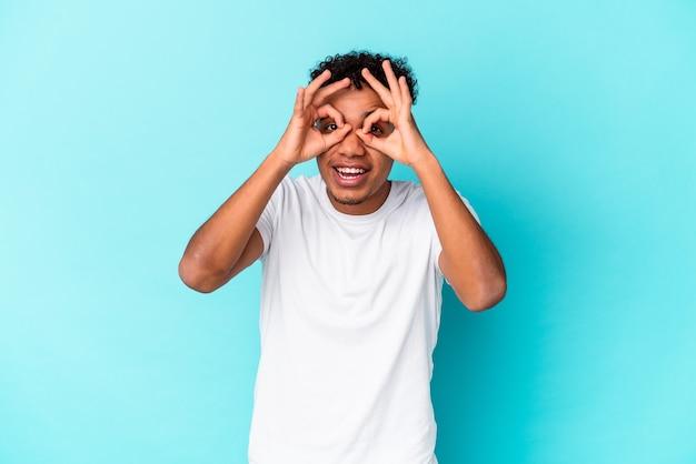 青で隔離の若いアフリカ系アメリカ人の巻き毛の男は、目の上に大丈夫サインを示しています