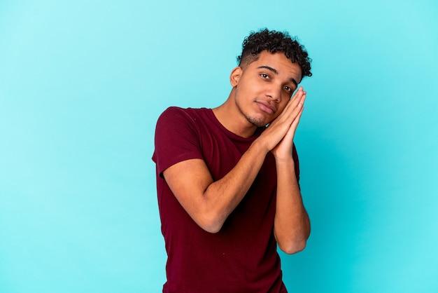 手で口を覆う疲れたジェスチャーを示す青いあくびで孤立した若いアフリカ系アメリカ人の巻き毛の男。