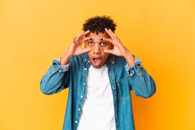 Молодой афро-американский кудрявый мужчина изолирован на фиолетовом, держа глаза открытыми, чтобы найти возможность успеха.