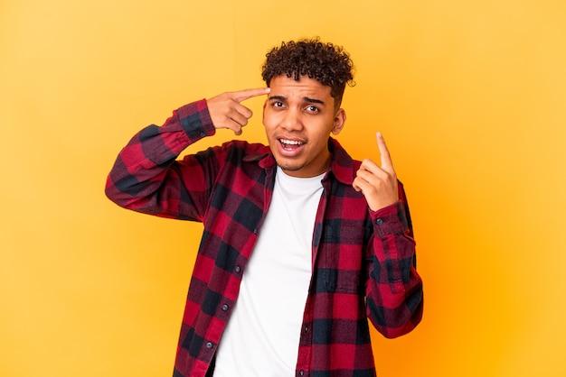 人差し指で失望のジェスチャーを示す紫色に分離された若いアフリカ系アメリカ人の巻き毛の男。