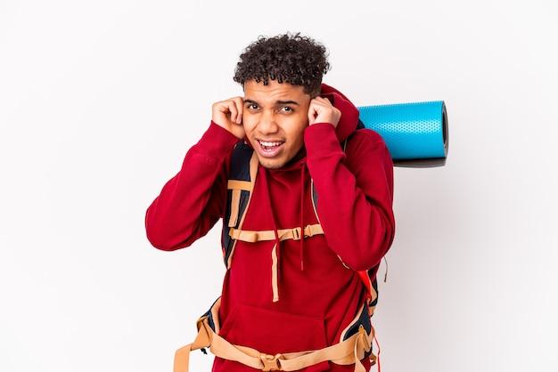 若いアフリカ系アメリカ人の巻き毛の旅行者の男は、手で耳を覆って孤立しました。