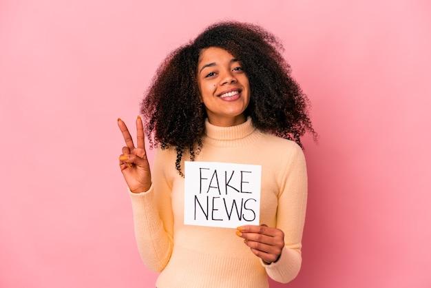 指で2番目を示すプラカードに偽のニュースを保持している若いアフリカ系アメリカ人の巻き毛の女性。