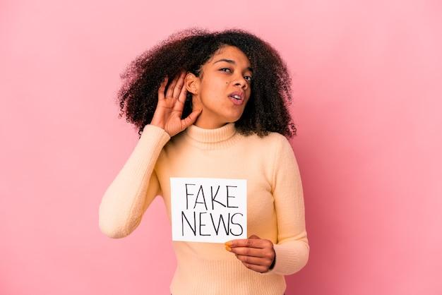 ゴシップを聴こうとしているプラカードに偽のニュースを保持している若いアフリカ系アメリカ人の巻き毛の女性。